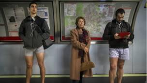 """Пассажир в обычной одежде между участниками акции """"день без штанов"""""""
