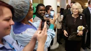लंदन के किंग्स कॉलेज अस्पताल के कर्मचारी ब्रिटेन के युवराज प्रिंस चार्ल्स की पत्नी कैमिला की तस्वीर लेते हुए .