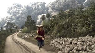 राख से बचने के प्रयास में भागती महिला.