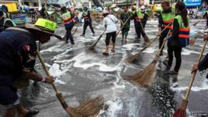 सरकार विरोधी प्रदर्शनकारी सड़कें साफ़ करते हुए