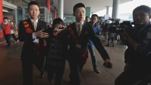 Một phụ nữ đang la khóc và được các nhân viên dẫn tới một xe bus ở khu vực sân bay dành cho thân nhân các hành khách.