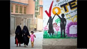 Mujeres y una niña pasan en la calle junto a una pancarta electoral Foto Anja Niedringhaus