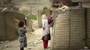 Niños jugando cerca de un sitio de registro electoral