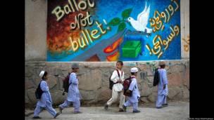 Niños con mochilas en sus espaldas pasan junto a una pancarta electoral