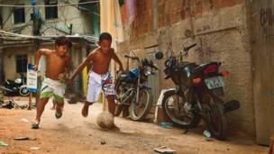 """Rocinha, Rio de Janeiro'daki """"favela""""da - gecekondu mahallesinde - çocuklar top için kavga ediyor."""