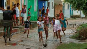 Penedo, Alagoas'ın sokaklarında kız çocukları çamurlu topun ardından koşturuyor. Caio Vilela