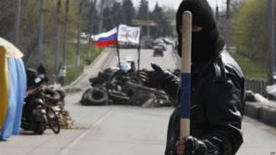 Un miliciano prorruso sostiene un palo de forma amenazante mientras resguarda una barricada en la que ondea la bandera rusa. Esto ocurrió en un camino que conduce a la ciudad ucraniana oriental de Slavyansk.
