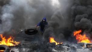 Un manifestante prorruso prende fuego a llantas en preparación para la batalla con las Berkut –las fuerzas policiales especiales de Ucrania– en las afueras de la ciudad de Slavyansk, al este de Ucrania.