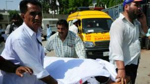 कराची धमाका, घायल को अस्पताल पहुंचाते लोग