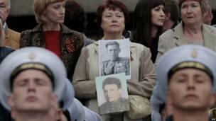 Una mujer sostiene fotos de familiares que pelearon en la Segunda Guerra Mundial