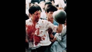 Un manifestante cubierto de sangre sostiene un casco de un soldado. 4 de junio de 1989. REUTERS