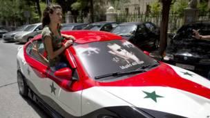 सीरिया में एक महिला, राष्ट्रध्वज में रंगी हुई कार के साथ