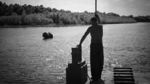 Человек с багром на реке