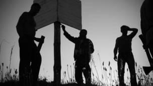 Люди стоят у берегового навигационного знака