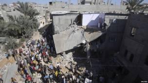 Palestinos reunidos frente a una casa en ruinas en Jan Yunis
