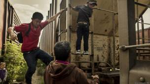 Migrantes subiendo a vagon de tren