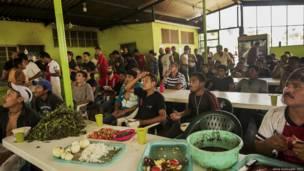 Migrantes comen y ven partido de fútbol