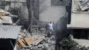 En la imagen, un hombre espera con los brazos levantados sobre los esconbros de un edificio en la ciudad de Gaza. Crédito: AP.