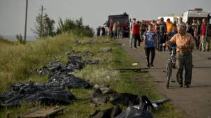 La gente pasa junto a los restos de las víctimas en sacos plásticos