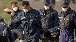 Rescatistas llevan restos de víctimas