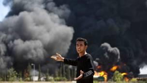 ये व्यक्ति इसराइल की तरफ़ से किए गए हमले में जल कर राख हो रहे ईधन टैंकों की ओर इशारा कर रहा है.