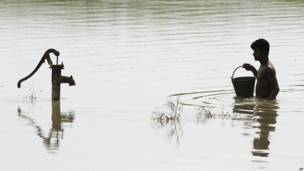 बाढ़ के पानी में घिरे से हैंडपंप से पानी लेने जाता एक व्यक्ति.