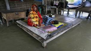 अपने बीमार बच्चे के साथ बाढ़ के पानी से घिरे घर में बैठी एक महिला.