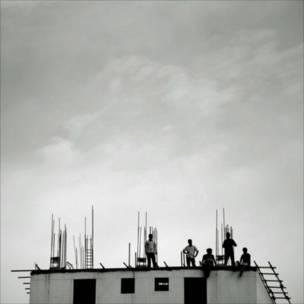 मालदीव की राजधानी माले की एक निर्माणाधीन गगनचुंबी इमारत के शिखर पर काम करते मजदूर