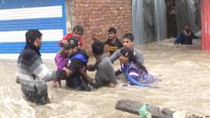 श्रीनगर में बाढ़ के पानी में घिरे हुए घरों से निकलकर सुरक्षित स्थानों की ओर जाते लोग.