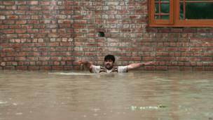 श्रीनगर में बाढ़ के पानी में घिर जाने के बाद मदद की अपील करता एक व्यक्ति.