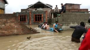 श्रीनगर के बाहरी इलाक़े में नाव में बैठककर सुरक्षित स्थान की ओर जाता एक परिवार.