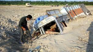 जम्मू के पास मलबे में दबे एक ट्रक को देखता एक व्यक्ति.