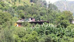 रजौरी ज़िले के एक गांव में अपने घर की छत पर बैठे लोग.