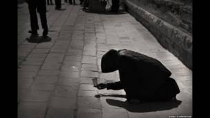 الصورة الظلية البعيدة، امرأة تتسول في الشارع. سارة سكاربورو