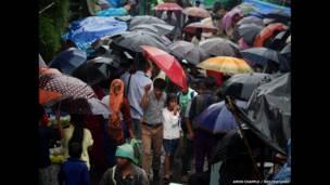 مجموعة من الناس تسير في ماوسينرام وهم يرتدون مظلاتهم الشهيرة.