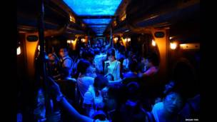 A woman spotlighted by the glow of her phone on a crowded train inOcean Park in Hong Kong.  Brian Yen