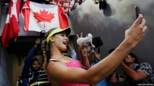 कनाडा की टेनिस खिलाड़ी यूजिनी बोकार्ड नीदरलैंड्स की कीकी बर्टेंस को ऑस्ट्रेलियन ओपन का एक मैच में हराने के बाद एक दर्शक के फोन से सेल्फ़ी लेते हुए.