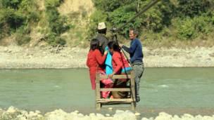 يعود المواطنون إلى قريتهم عبر نهر ترشولي