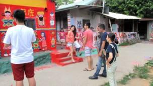 台中彩虹眷村內遊客駐足觀賞一幅畫作