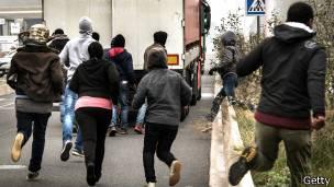 inmigrantes corriendo tras un camión que se dirige al Eurotúnel en Calais, Francia
