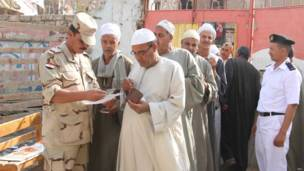 أحد أفراد الجيش يفحص هوية ناخب