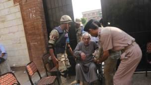 رجل مسن معاق يدخل لجنة الاقتراع للتصويت