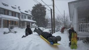 बर्फ़ पर खेलने का मज़ा लेते बच्चे