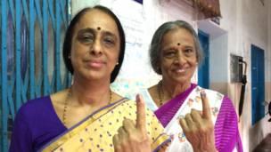 कोच्चि के एक मतदान केंद्र पर मतदान के बाद स्याही लगी ऊंगली दिखातीं मतदाता.