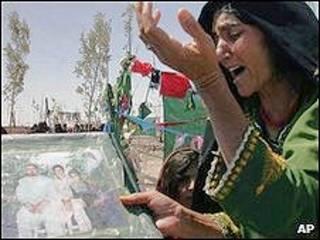 Mulher afegã mostra foto de familiares mortos em ataque liderado pelos EUA em agosto de 2008