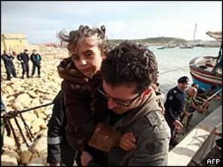 Imigrante leva filha ao desembarcar de barco de pesca em Malta, vindo da África