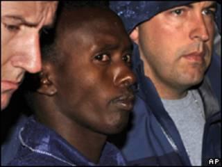 Suposto pirata somali (ao centro) é escoltado por policiais ao desembarcar nos EUA, na última segunda-feira (AP)