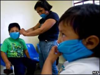 Mulher coloca máscaras em seus filhos na Cidade do México (AFP)