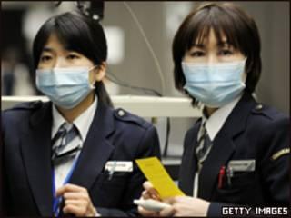 Funcionárias do Aeroporto de Narita, no Japão, controlam a chegada de passageiros
