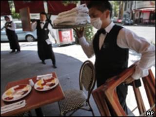 Garçom usando máscara contra a gripe recolhe pratos de restaurante fechado na Cidade do México (AP, 28/4)